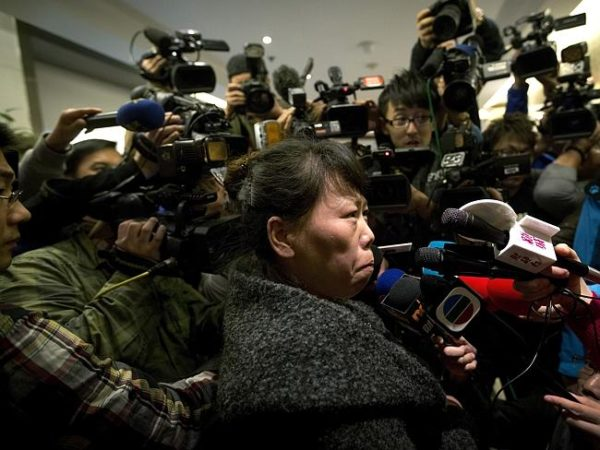 A family member of a passenger from flight MH370 anxiously awaits news