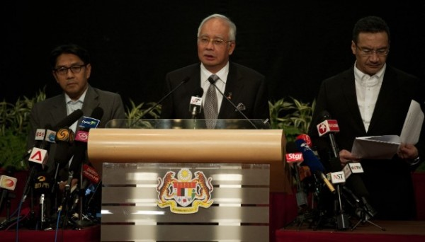 "Malaysian Prime Minister Najib Razak, center, delivers a statement about the flight March 24 in Kuala Lumpur, Malaysia. Razak's announcement came after the airline sent a text message to relatives saying it ""deeply regrets that we have to assume beyond any reasonable doubt that MH 370 has been lost and that none of those onboard survived."""